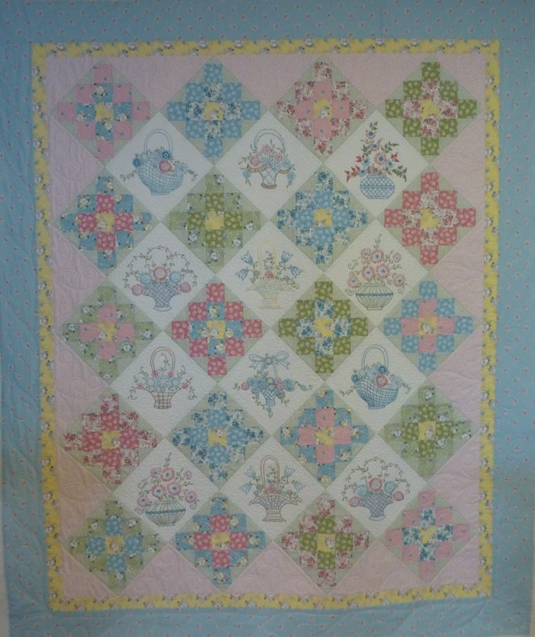 The pieced blocks have a freehand quilting design and the embroidered blocks  have outlining and a small meander. The setting blocks and borders are a ...